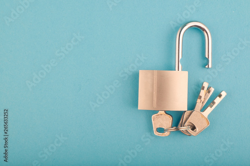 Photographie  unlocked Padlock and bunch of key on the blue background