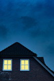 Country house with illuminated windows in twilight. - 265638486