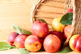 Nectarines in basket on a wooden table.