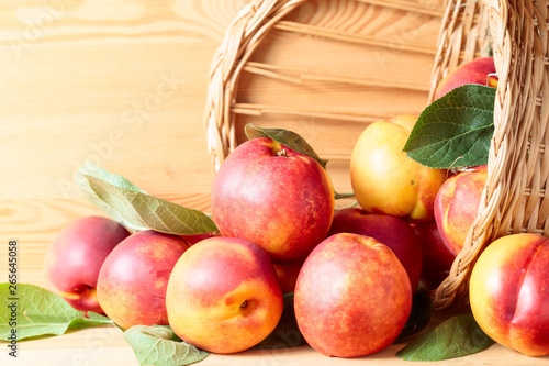 Poster de jardin Nature Nectarines in basket on a wooden table.