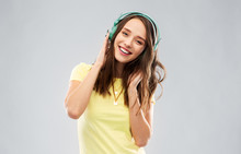 Music, Technology And People Concept - Happy Young Woman Or Teenage Girl With Headphones Over Grey Background