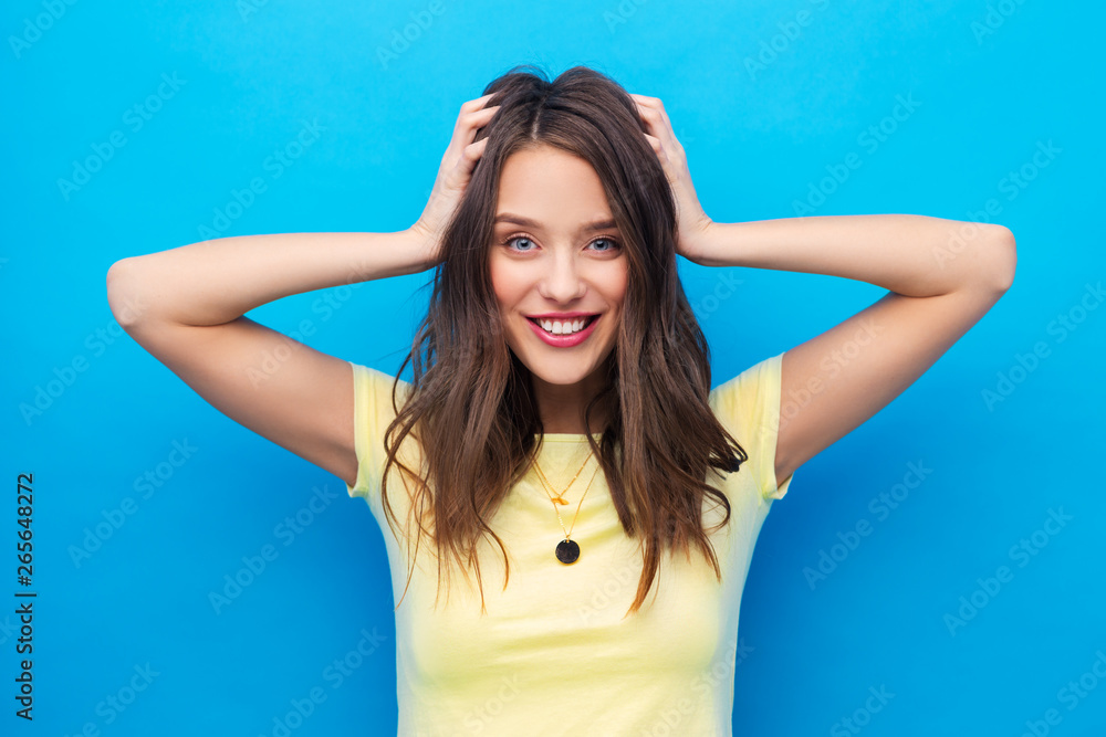 Fototapety, obrazy: people concept - smiling young woman or teenage girl in yellow t-shirt holding to her head over bright blue background