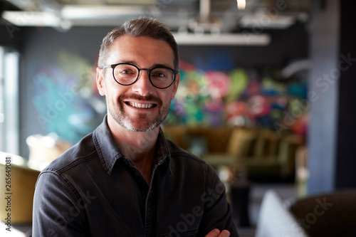 fototapeta na lodówkę Middle aged white male creative in casual office lounge area looks to camera smiling, close up
