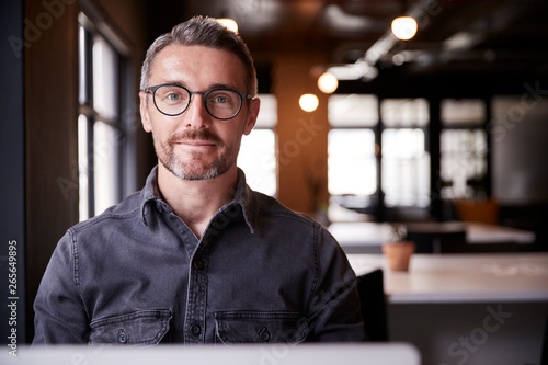 Middle aged white male creative sitting in an office smiling to camera, head and Poster Mural XXL