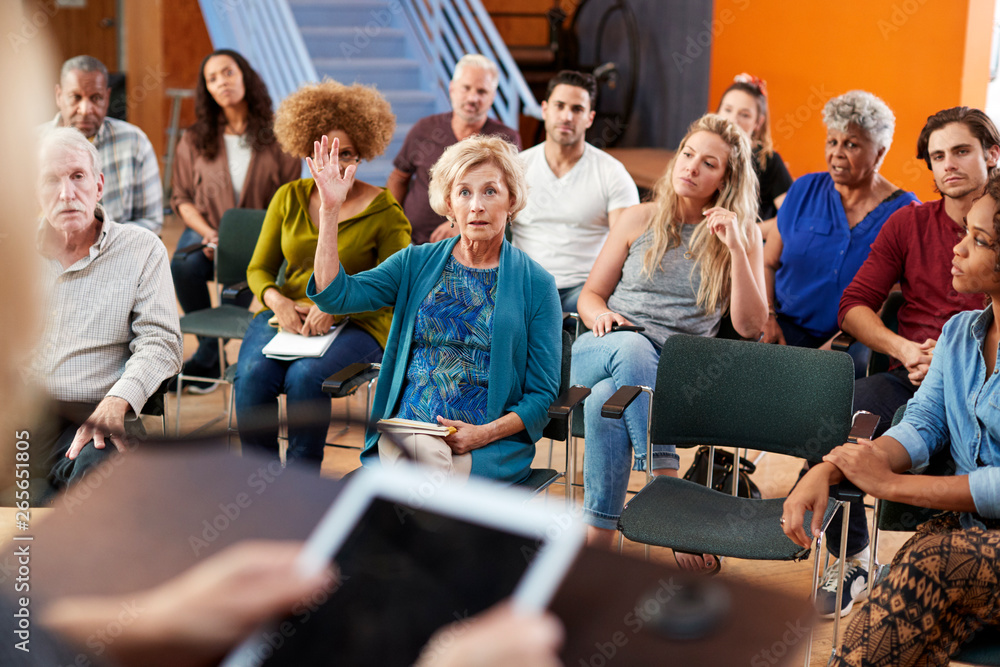 Fototapeta Woman Asking Question At Group Neighborhood Meeting In Community Center