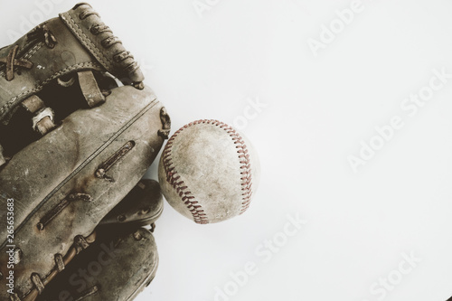 Fényképezés  Old rough and rugged baseball with glove on white background, copy space for vintage sports concept