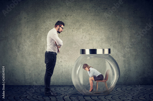 Fototapeta Authoritarian boss businessman looking at a glass jar with captured woman inside