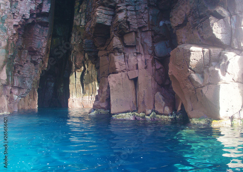 Grotto in the lagoon with azure blue transparent water with stones and rocks.