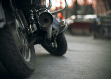 Part Of A Brand-new Motorcycle With Wheels And A Dirty Exhaust Pipe. The Motorcycle Stands On The Asphalt Road In The Dark Evening And Against The Background The Red Light Of The Traffic Light Burns.
