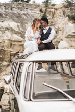 Happy Wedding Multiracial Couple Sitting On The Roof Of A Vintage Green Bus, Looking Each Other, Holding Hands. Wedding Story In The Canyon