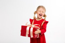 Portrait Of Little Girl In Red Dress On Isolated White Background. Smiling Girl In Shirt With Gifts In Hands Looking At Camera. Isolated Gray Background. The Concept Of Celebrating, Giving And Receivi