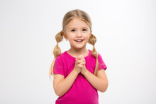 Baby Girl Blonde Girl In Pink T-shirt On White Smiling Background.Charming Slim Girl With Long Tails On The Head And A Pink T-shirt. Close-up-Isolated On White Background