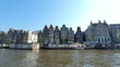 Magnificent architecture of Amsterdam houses. The houses are tilted in different directions. The facades of the houses of Amsterdam on a Sunny day