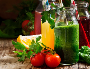 Food and drinks, selection of vegetable and fruit juices and smoothies in glass bottles with ingredients, set on rustic wooden table, selective focus