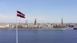 Aerial shot of the Latvian flag with the city of Riga in the background