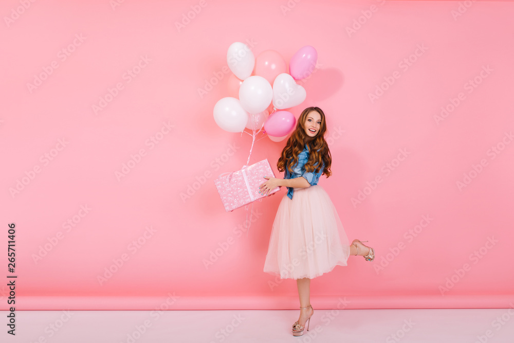 Fototapety, obrazy: Full-length portrait of adorable birthday girl with curly hair wearing high heel shoes, holding present in cute box. Graceful slim young woman received gift with colorful helium balloons on holiday