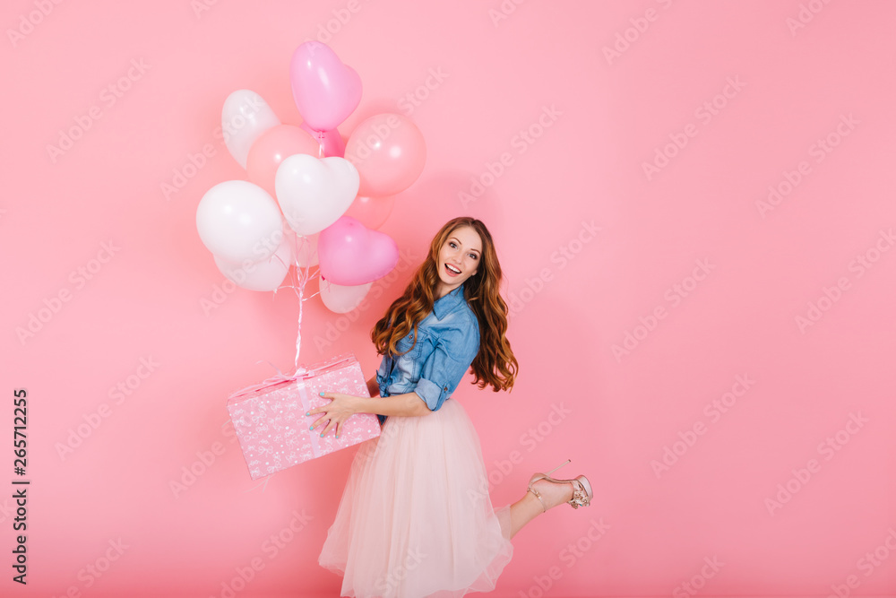 Fototapety, obrazy: Excited long-haired girl in lush midi skirt standing on one leg, holding cute birthday present. Charming curly young woman in stylish outfit going to friend's party with gift and colorful balloons