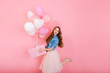 canvas print picture - Excited long-haired girl in lush midi skirt standing on one leg, holding cute birthday present. Charming curly young woman in stylish outfit going to friend's party with gift and colorful balloons
