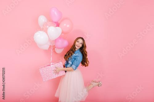 Fotografie, Obraz  Excited long-haired girl in lush midi skirt standing on one leg, holding cute birthday present