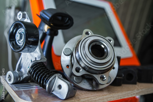 Car parts on a table with a computer in the background with a shallow depth of f Canvas Print