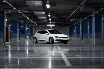 Exterior of white modern sport car at parking at evening time.
