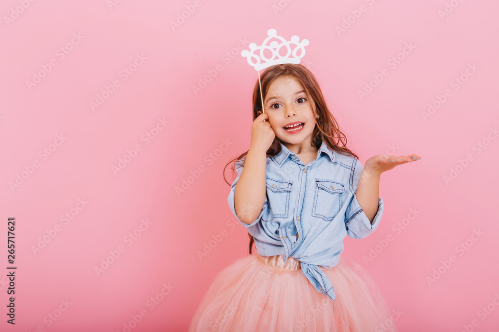 Fototapeta Joyful little girl with long brunette hair in tulle skirt holding princess crown on head isolated on pink background. Celebrating brightful carnival for kids, expressing positivity of birthday party