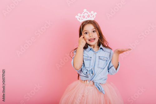 Joyful little girl with long brunette hair in tulle skirt holding princess crown on head isolated on pink background Wallpaper Mural