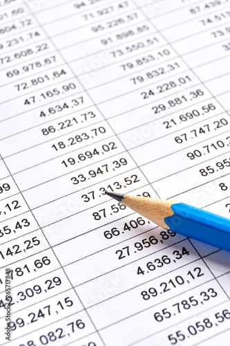 Blue pencil on a sheet of white paper with printed financial numerical data table with columns Canvas Print
