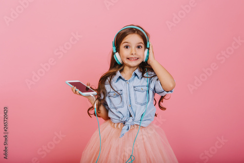 Fotografía  Expressing positivity of happy child listening to music through blue headphones isolated on pink background
