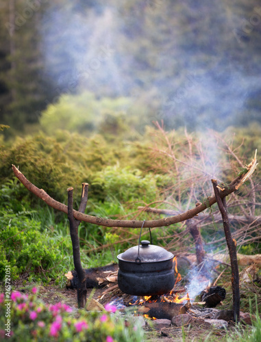 Fotografía  Kettle on fire in the forest during hike or trekking in nature.