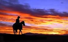 Cowboy On Horseback Rides Into The Sunset