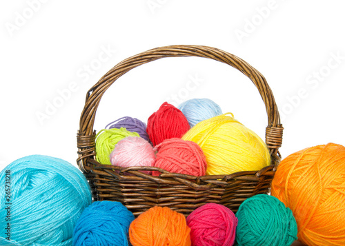 Obraz na plátne Brown woven basket full of colorful balls of yarn overflowing yarn onto table, isolated on white background
