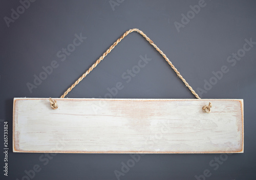 Fotografía  Vintage wooden sign with rope hanging on a gray background