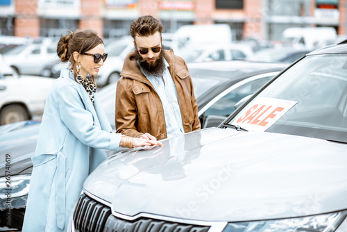 Fotografía Young stylish couple choosing luxury car to buy on the open ground of the dealer