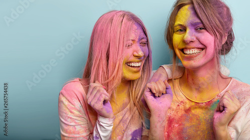 Photo  Cropped image of joyful young women laugh and clench fists, have fun together on