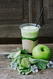 Green apple smoothie in glass and kale leaves on wooden table - 265754812