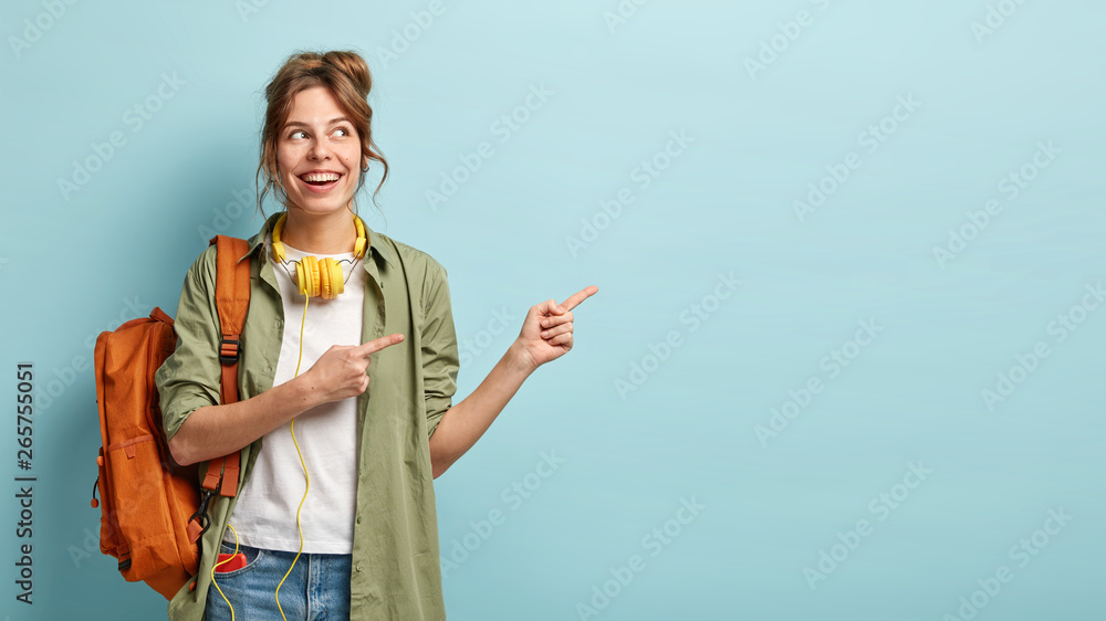 Fototapeta Positive European female teenager uses modern technologies for entertainment, points aside on free space, dressed in loose shirt and jeans, carries backpack, promotos something, poses indoor
