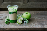 Green apple smoothie in glass and kale leaves on wooden table - 265755017