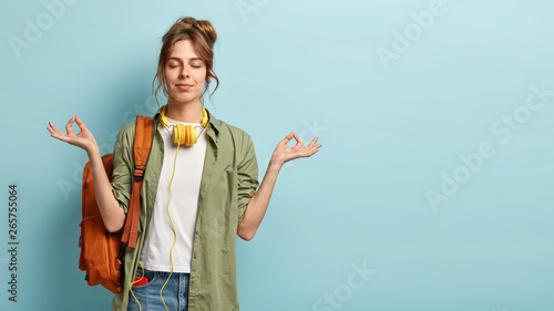 Foto Photo of relaxed student keeps hands in mudra gesture, keeps eyes closed, listen
