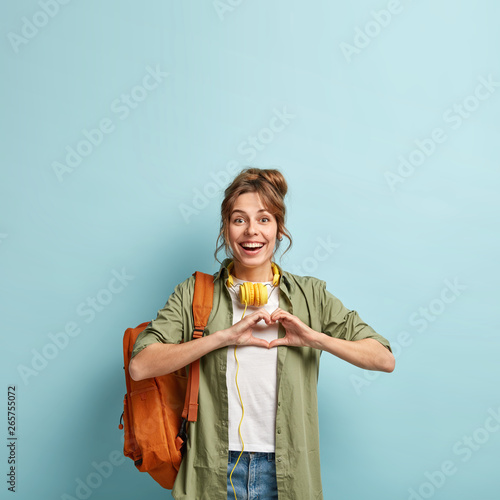 Fototapeta  Smiling cheerful college student makes heart gesture, expresses sympathy to grou