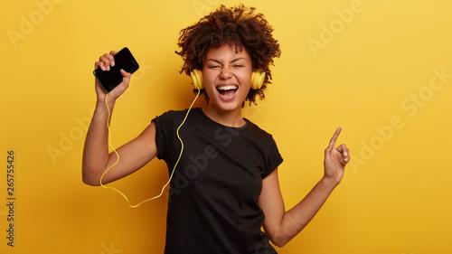 Fotografia, Obraz Funny dark skinned female feels great, dances to rhythm, shakes raised hands, si