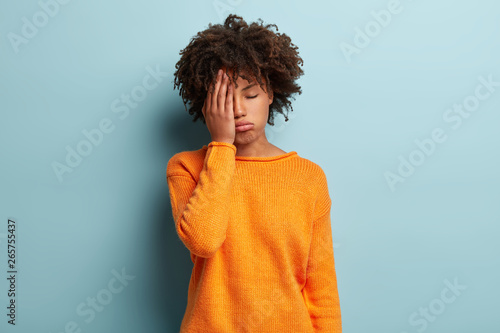Fotografia Photo of tired dark skinned female covers face, closes eyes, feels fatigue, needs good rest, dressed in orange jumper, has sleepy expression, isolated over blue background