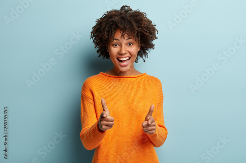 Pinturas sobre lienzo  Joyous pretty African American lady makes finger gun gesture at camera, expresses choice, smiles broadly, dressed in orange jumper, isolated over blue background, says you are chosen