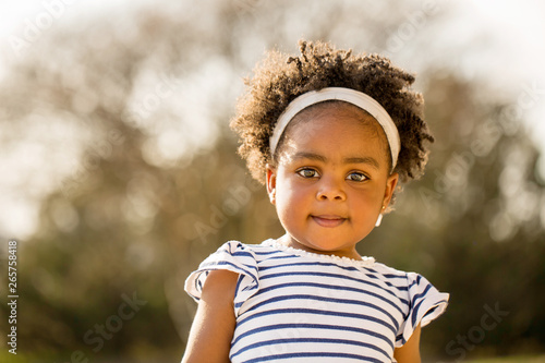 Happy little girl laughing and smiling outside. Wallpaper Mural