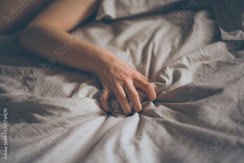 Hand sign orgasm of woman on white bed Fototapete