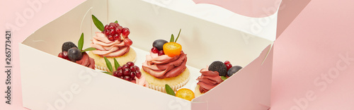 panoramic shot of cupcakes with berries and fruits in cardboard box isolated on Canvas Print