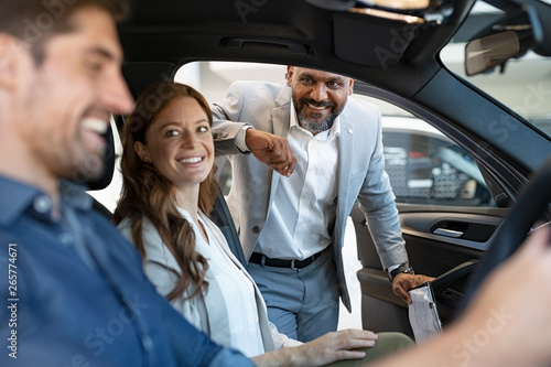 Salesman showing new car to couple Poster Mural XXL