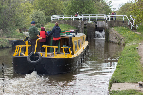 A family steers their boat towards the lock at Hirst Wood watched by bystanders Obraz na płótnie