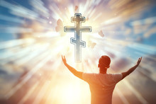 Man On The Background Of The Symbol Of Christianity, Prayer, Orthodox Cross On The Background Of The Sunset. The Concept Of Hope, Faith, Religion, A Symbol Of Freedom.