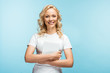 Leinwandbild Motiv happy blonde woman looking at camera while holding digital tablet on blue